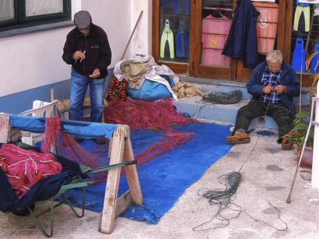 pescatori che riparano le reti